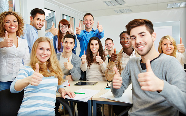 Eine fröhliche Seminargruppe zeigt einen Daumen nach oben